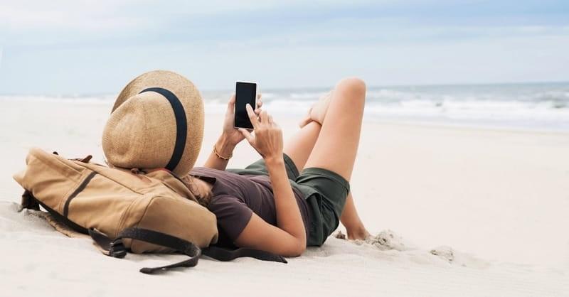 Mulher usando o celular na praia