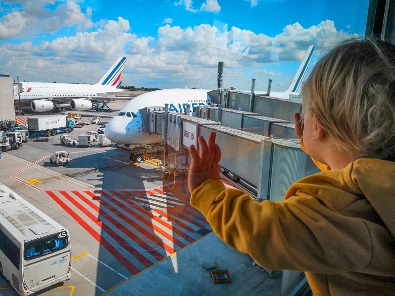 Criança olhando pela janela os aviões em aeroporto