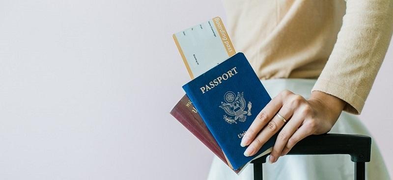 Mulher segurando passaporte e passagem aérea
