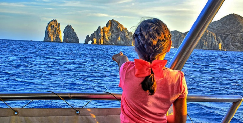 Criança apontando para o monumento El Arco em Los Cabos