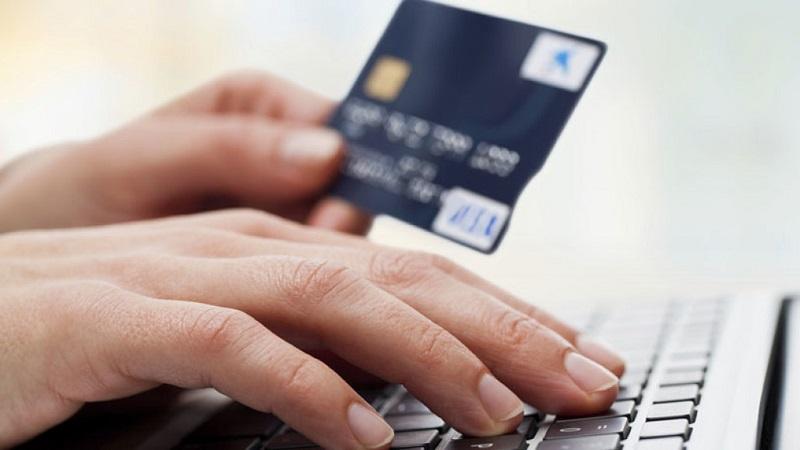 Pessoa com cartão e computador