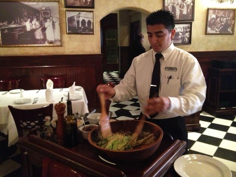 Garçom produzindo salada Caesar no Caesar's Restaurante