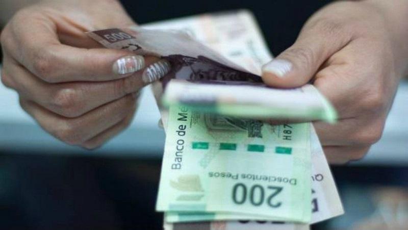 Pessoa contando pesos mexicanos