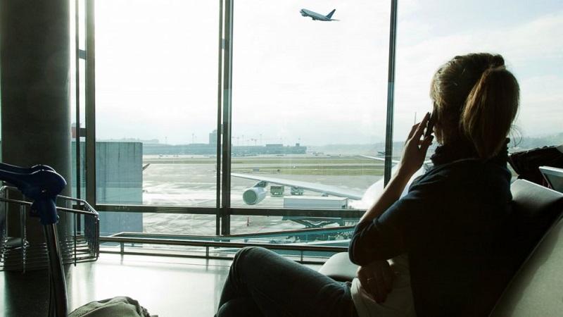 Menina aguardando voo em aeroporto