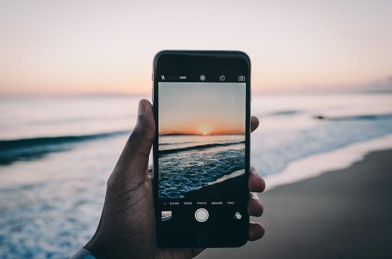 Usando o celular para fotografar praia